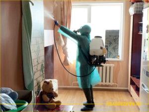 Мужчина дезинсектор в специальном костюме обрабатывает квартиру от тараканов
