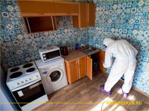 Дезинсектор обрабатывает под раковиной на кухне от тараканов